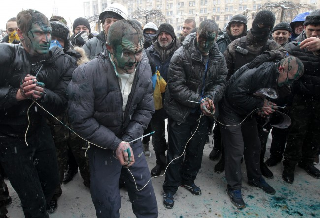 "Pro-government hired thugs, referred to as ""titushki"" are captured by protesters in central Kiev, Ukraine, Wednesday, Jan. 22, 2014. Anti-government protesters tied the suspected hired thugs, stained them with paint and then released them. Police in Ukraine's capital on Wednesday tore down protester barricades and chased demonstrators away from the site of violent clashes."