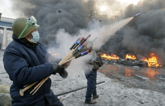 In this file photo taken on Thursday, Jan. 23, 2014, A protester aims fireworks at police during clashes, in central Kiev, Ukraine. Thick black smoke from burning tires engulfed parts of downtown Kiev as an ultimatum issued by the opposition to the president to call early elections or face street rage was set to expire with no sign of a compromise on Thursday.