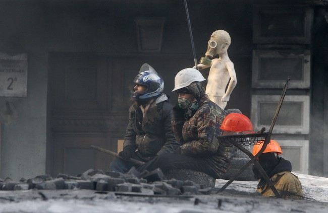 Protesters sit next to a shop mannequin as they guard the barricades in front of riot police in Kiev, Ukraine, Friday, Jan. 24, 2014.