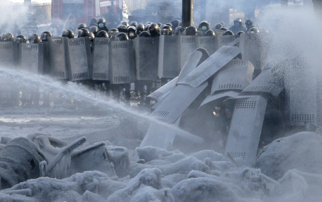 Riot police shoot water from water cannon against protesters during a clash in central Kiev, Ukraine, Saturday Jan. 25, 2014. Ukraine's Interior Ministry has accused protesters in Kiev of capturing two of its officers as violent clashes have resumed in the capital and anti-government riots spread across Ukraine.
