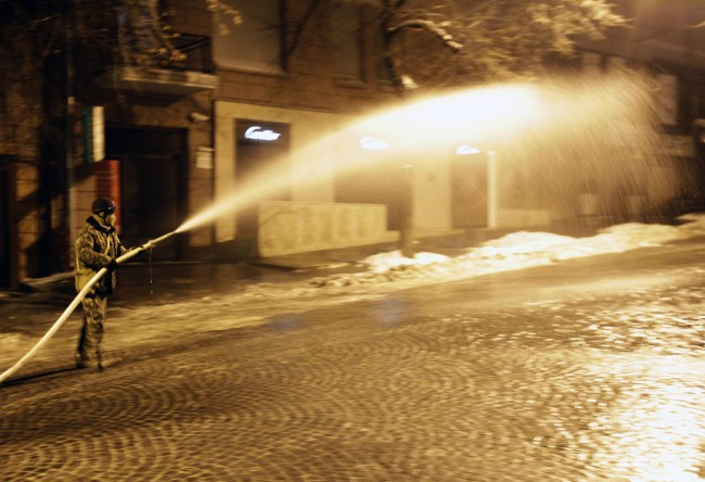 A protester sprays water on a street in the hopes it will freeze, thus making it inaccessible to police in front of the Justice Ministry in Kiev, Ukraine, Monday Jan. 27, 2014. Protesters seized the Justice Ministry building Sunday night, adding another government building to the several already occupied by the opposition.