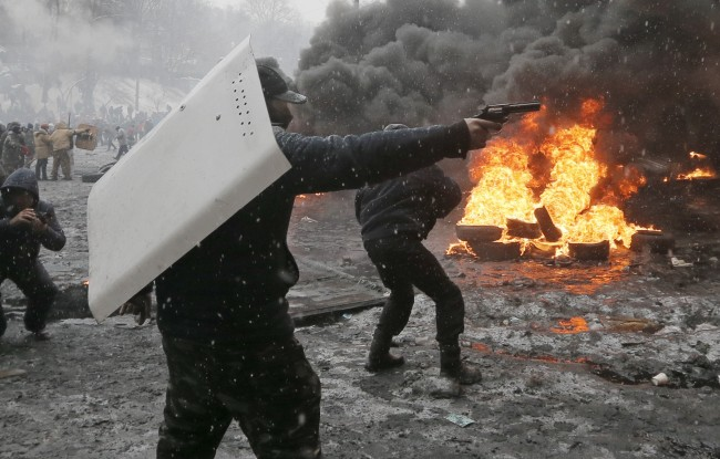In this Wednesday, Jan. 22, 2014 file photo a protester points a handgun during a clash with police in central Kiev, Ukraine. After two months of anti-government protests, modern Ukraine has never been so bitterly polarized. To be sure, Ukraine has long been divided. Russia and Europe have vied for dominance for centuries, causing deep cultural differences between the mostly Ukrainian-speaking western and central regions on the one hand, and the Russian-speaking east and south on the other. But as the crisis has deepened, each side has grown stronger in its convictions, and those who stood in the middle have been forced to choose sides.