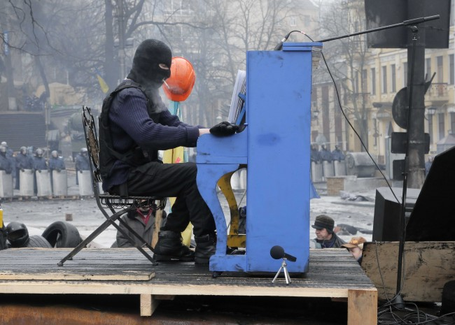An opposition supporter plays the piano on barricades in front of riot police in central Kiev, Ukraine, Monday, Feb. 10, 2014. Ukraine has been rocked by nearly three months of anti-government protests sparked by President Viktor Yanukovich's refusal to sign a wide-ranging trade agreement with the European Union.