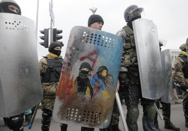 An opposition protester holds a shield depicting, what he said, is a self-portrait with his girlfriend in a sign of love on a Valentine's Day while protesters prepare for a rally in Kiev's Independence Square, the epicenter of the country's current unrest, Ukraine, Friday, Feb. 14, 2014.