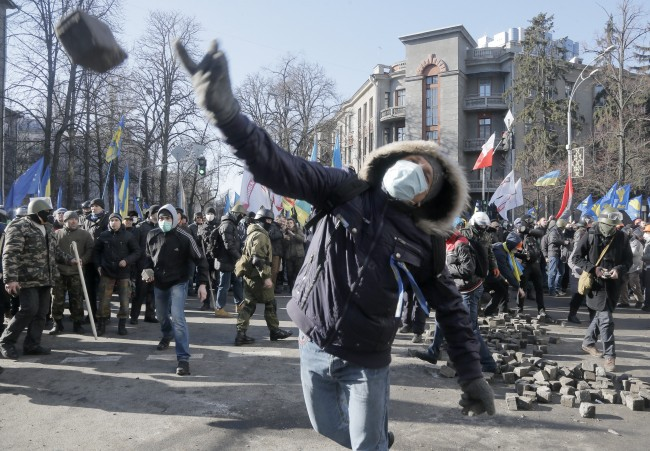 An anti-government protester throw a stone during clashes with riot police outside Ukraine's parliament in Kiev, Ukraine, Tuesday, Feb. 18, 2014. Thousands of angry anti-government protesters clashed with police in a new eruption of violence following new maneuvering by Russia and the European Union to gain influence over this former Soviet republic.