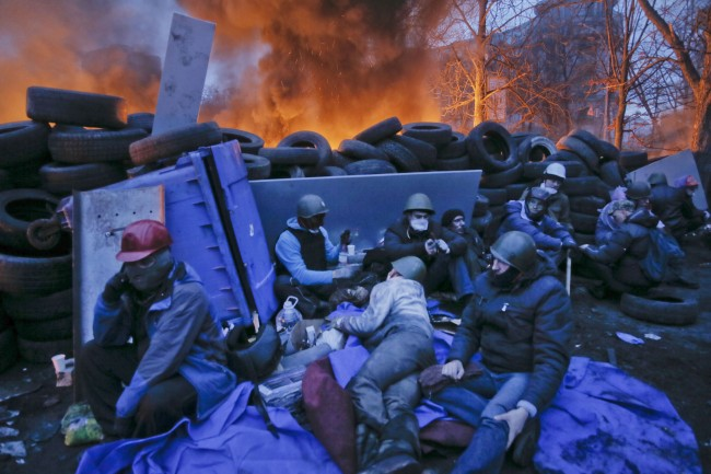 Activists have a rest at the burning barricades, on the side of bloody clashes close to Independence Square, the epicenter of the country's current unrest, Kiev, Ukraine, Thursday, Feb. 20, 2014. Fearing that a call for a truce was a ruse, protesters tossed firebombs and advanced upon police lines Thursday in Ukraine's embattled capital. Government snipers shot back and the almost medieval melee that ensued left scores of people dead.
