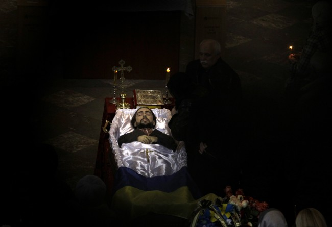 An open casket with the body of Bogdan Solchunuk, 28, lays in the centre of St. Paul and Peter church, during his funeral service in Lviv, western Ukraine, Saturday, Feb. 22, 2014. Church services were held Saturday in the pro-opposition stronghold of Lviv in the west of Ukraine for the locals who were killed in Kiev during the past week. Lviv activists say 19 of their people were killed in the violence at Maidan.
