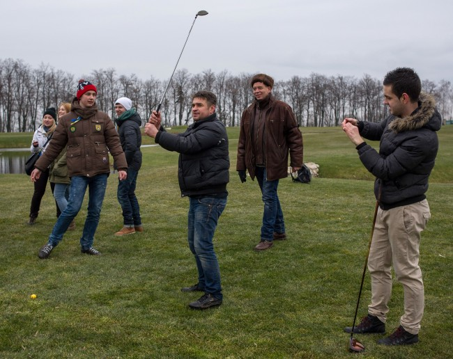Protesters try to play on a golf course at the Ukrainian President Yanukovych's countryside residence in Mezhyhirya, Kiev's region, Ukraine, Saturday, Feb, 22, 2014. Viktor Yanukovych is not in his official residence of Mezhyhirya, which is about 20 kilometres north of the capital. Ukrainian security and volunteers from among Independence Square protesters have joined forces to protect the presidential countryside retreat from vandalism and looting.