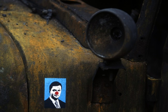 A sticker depicting Ukrainian President Viktor Yanukovych is placed on a burned military truck in Kiev, Ukraine, Sunday, Feb. 23, 2014. The Kiev protest camp at the center of the anti-President Viktor Yanukovych movement filled with more and more dedicated demonstrators Sunday morning setting up new tents after a day that saw a stunning reversal of fortune in a political standoff that has left scores dead and worried the United States, Europe and Russia.