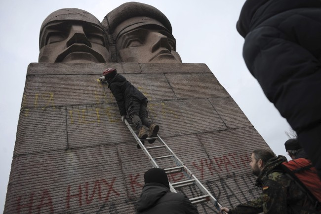 People paint on the KGB officers monument in Kiev, Ukraine, Sunday, Feb. 23, 2014. A top Ukrainian opposition figure assumed presidential powers Sunday, plunging Ukraine into new uncertainty after a deadly political standoff and boosting long-jailed Yulia Tymoshenko's chances at a return to power. The whereabouts and legitimacy of President Viktor Yanukovych are unclear after he left the capital for his support base in eastern Ukraine.