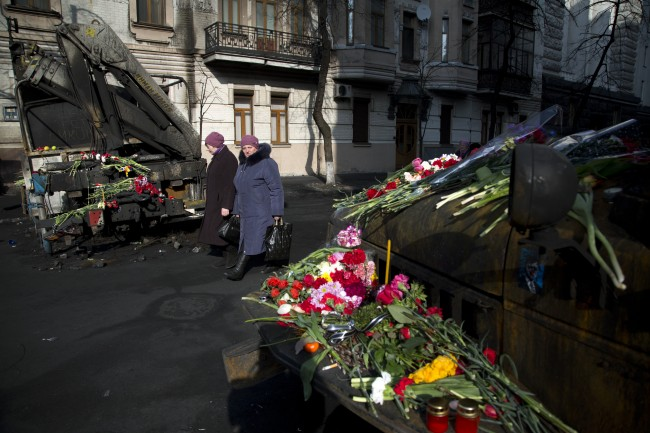 Women pass by flowers laid on burned military vehicles in central Kiev, Ukraine, Monday, Feb. 24, 2014. Ukraine's acting government issued a warrant Monday for the arrest of President Viktor Yanukovych, last reportedly seen in the pro-Russian Black Sea peninsula of Crimea, accusing him of mass crimes against protesters who stood up for months against his rule.