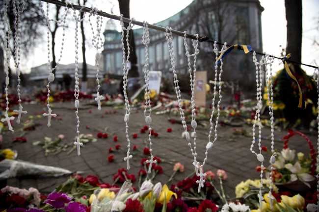 Rosary beads hang on a barricade in Kiev's Independence Square, the epicenter of the country's current unrest, Ukraine, Monday, Feb. 24, 2014. Ukraine's acting government issued a warrant Monday for the arrest of President Viktor Yanukovych, last reportedly seen in the pro-Russian Black Sea peninsula of Crimea, accusing him of mass crimes against protesters who stood up for months against his rule.