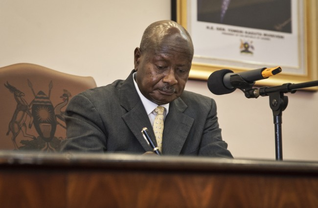 "Uganda's President Yoweri Museveni signs a new anti-gay bill that sets harsh penalties for homosexual sex, in Entebbe, Uganda Monday, Feb. 24, 2014. Museveni on Monday signed the controversial anti-gay bill into law, with penalties including 14 years in jail for first-time offenders and life imprisonment as the maximum penalty for ""aggravated homosexuality"", saying it is needed to deter what he called the West's ""social imperialism"" promoting homosexuality in Africa. (AP Photo/Rebecca Vassie)"