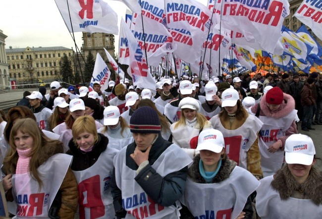 Young activists for Russia's United Russia party march in support of Ukraine's pro-Moscow Regions Party on Independence square in Kiev, Ukraine, Wednesday, March, 22, 2006. Forty five parties are standing in Sunday's critical parliamentary elections. Under constitutional reforms, key presidential powers will pass to parliament. The slogans on the flags and tents reads Our Ukraine.
