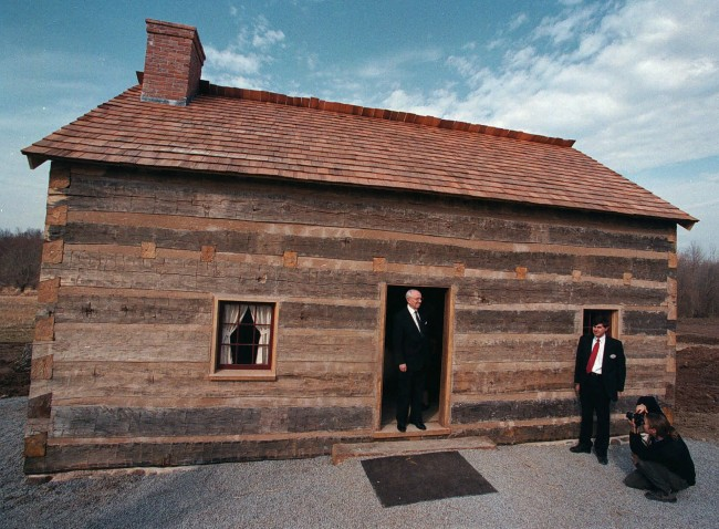 Mormon church President Gordon B. Hinckley poses in the doorway of a replica of the log house Friday, March 27, 1998 in Palmyra, N.Y., where church founder Joseph Smith lived when he encountered his first vision that led to the formation of the Mormons. Smith was 17 years old in 1823 when he was visited by the angel Moroni in his bedroom, according to the church's history. Three years earlier, Smith said he saw God and Jesus Christ while praying in a nearby maple grove. Smith claimed the angel led him to a buried cache of gold plates on nearby Cumorah Hill that he translated into the Book of Mormon, one of four books in the church's scriptural canon, which includes the Bible. The first six believers formally organized the church in 1830 in Fayette.