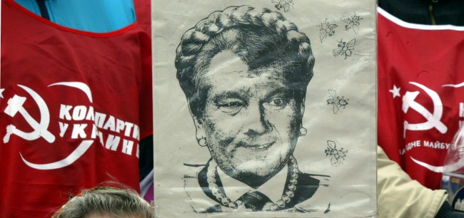 Communist Party members, supporters of Ukrainian Prime Minister Viktor Yanukovych hold caricature depicting President Yuschenko with the hair-do of Opposition leader Yulia Tymoshenko during a rally in Kiev, Ukraine, Thursday, April 12, 2007. Ukraine's President Viktor Yushchenko said Thursday that his order to dissolve parliament and hold new elections will stand, continuing a war of wills with the defiant premier who appeared to signal his readiness for a compromise.