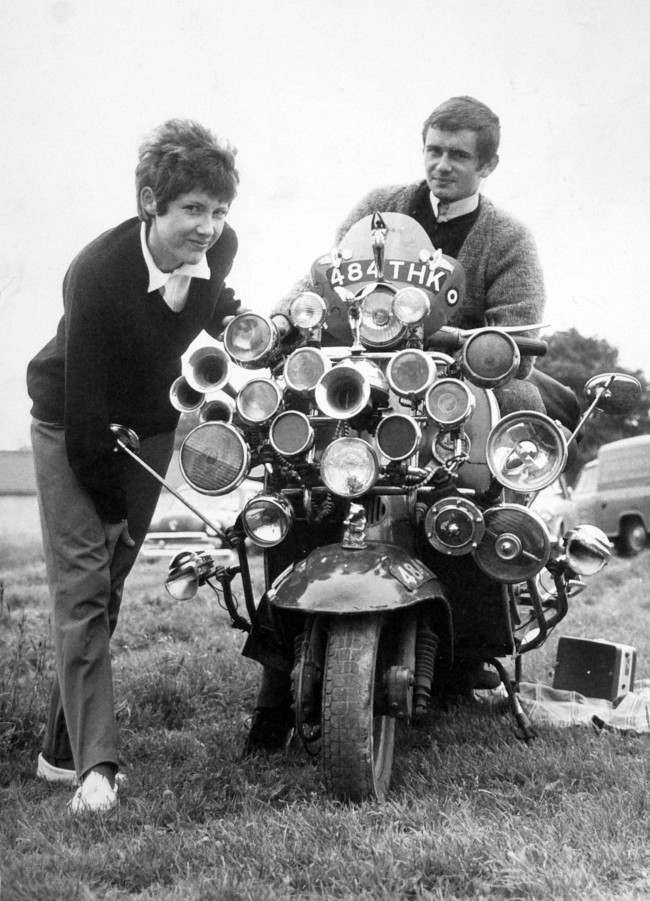 The modern fad for having as much sound and light as possible on your scooter reached the Epsom Downs for Derby Day. Proud owners of this laden-down Vespa scooter are Roy Young and Linda Jarvis.   Date: 31/05/1964