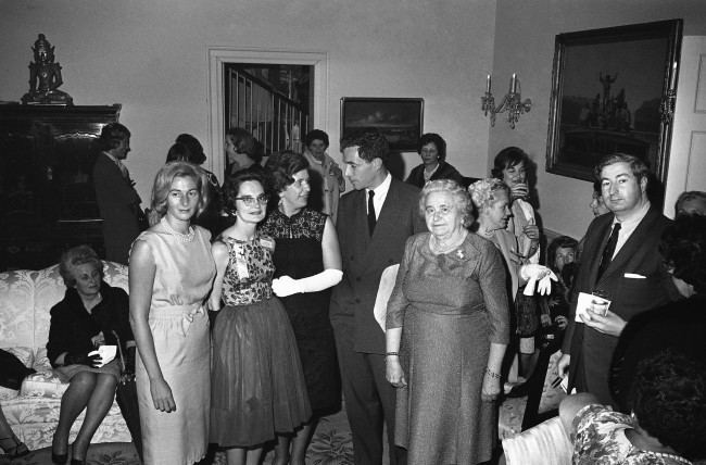 Rhode Islanders attending the campaign conference of democratic Women in Washington on May 1, 1964 were guests of Sen. and Mrs. Claiborne Pell, D-R.I., at their home in the capital. What had been planned as a garden party had to be held indoors because of the week-long rains. Group from left: Mrs. Nuala Pell; Mrs. Anne McGeough, Mrs. Constance Savard, Sen.Claiborne Pell and Mrs. Kathleen McDonald. Mrs. Pell is wearing light colored sleeveless dress standing at left of group.