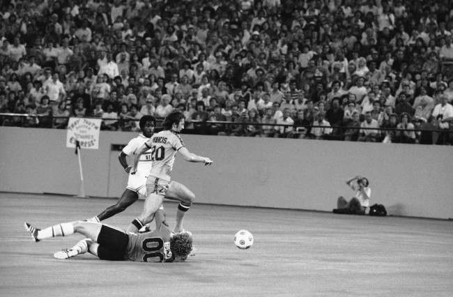 Detroit Express' Trevor Francis (20) breaks past Ft. Lauderdale Strikers' goalie Ian Turner (00), on the ground, with Strikers' Colin Fowles chasing him in the first half of second round of the NASL playoff in Pontiac Silverdome, Aug. 16, 1978 in Pontiac. Francis was tripped up by Turner's arm and lost control of the ball. (AP Photo)   Date: 16/08/1978