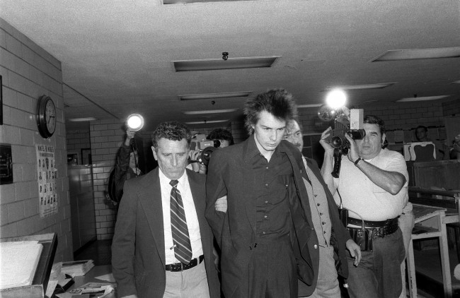 New York police escort British punk rock musician Sid Vicious, or John Simon Ritchie, former bass guitarist of the Sex Pistols, shortly before he was charged with murder in the stabbing death of his girlfriend, Nancy Laura Spungen, at New York's Chelsea Hotel, Oct. 13, 1978.