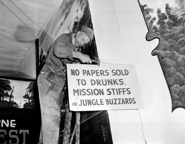 Mike Jonas affixes a sign in the Hobo News office, a union shop employing 15 people, at the newspaper's new location on New York's 52nd St.