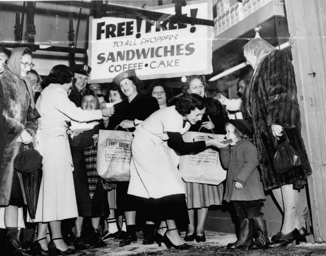 Hungry customers get coffee, sandwiches, and cake on the house at Fort Greene, retail market in Brooklyn, N.Y., January 27, 1949. Katherine O'Toole, three, receives a sandwich from Rena Kleiman as her mother does her shopping. Other buyers get theirs under the free for all sign. (AP Photo) Date: 27/01/1949