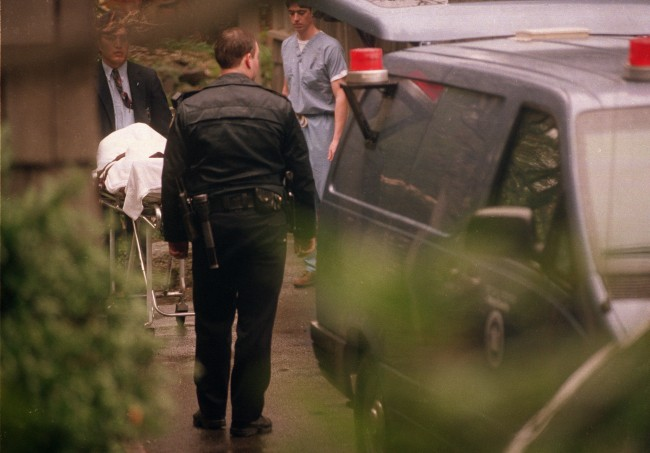 The body of Nirvana lead singer Kurt Cobain is taken to a medical examiner's van, after he was found dead earlier that day at his home in Seattle, Wash., on April 8, 1994. According to a police source, Cobain died from a self-inflicted shotgun wound, and a suicide note was found next to the body.