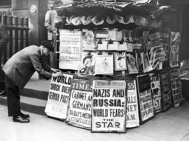 A news vendor sets up his placards in a London street August 22, 1939 so that even those who ride may read something of the international tension. (AP Photo)