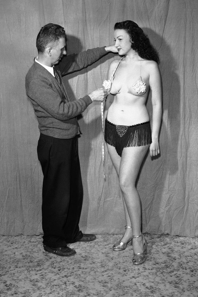 Even clothes that come off have to fit. Here, Charles Guyette, New York dealer in theatrical accessories, measures night-club stripper Sheila Ryan for addition to her wardrobe on Sept. 29, 1948. Guyette reports the G-string business is booming although prices have remained fairly constant. The every day, garden variety at $7.50, as it did before the war, Guyette reports. (AP Photo)