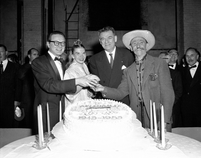 "At backstage theater party at the National Theater in Washington, D.C., lyricist Oscar Hammerstein II (second from right) and Original members of the cast of ""Oklahoma"" cut its 10th anniversary cake. From left are: Alfred Drake, who played the original male lead; Bambi Lynn, who played ""Aggie"" when the show opened in New York in 1943; Hammerstein, and Owen Martin, who is still playing ""Andrew Carnes."""
