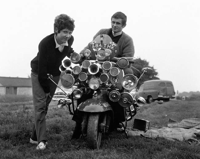 The modern fad for having as much sound and light as possible on your scooter reached the Epsom Downs for Derby Day. Proud owners are Roy Young and Linda Jarvis. Proud riders are Roy Young and Linda Jarvis at Derby Sunday on the Epsom Downs. Date: 31/05/1964