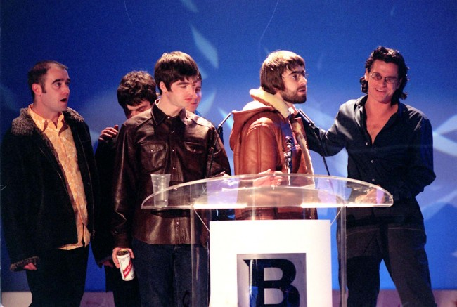 "Manchester pop group Oasis accept the Brit award for Best Video (for 'Wonderwall') from Inxs frontman Michael Hutchence (left) at a star-studded ceremony at London's Earl's Court. Liam Gallagher, with beard, confronted Hutchence, once linked to Gallagher's present girlfriend Patsy Kensit, and said ""Has-beens shouldn't present awards to going-t-be's'."