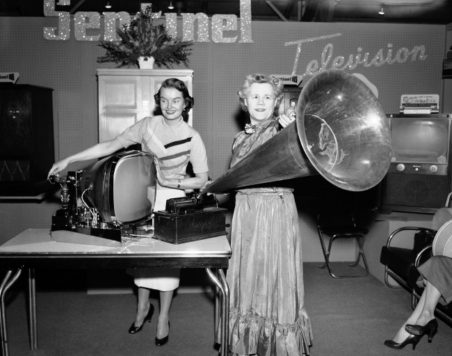 Jane Casey (left) and Jane Challis show progress in home entertainment at the Chicago Modern Living Exposition, March 27, 1953. The huge horn fitted onto the 1900 Edison Home Phonograph using a cylinder record. The item at left is a 1953 model Sentinel television chassis.