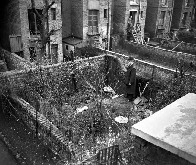 A policeman in the garden of 10 Rillington Place in Notting Hill, London, where police found human bones buried a few inches under the soil. They had been burned in an attempt to destroy them. The bodies of four strangled women have already been discovered at the address. Police are searching nationwide for suspect John Reginald Christie.
