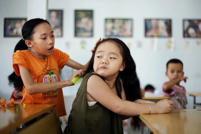 In this photo taken Aug. 7, 2012, Ho Thi Lang, left, combs Ngo Diep Uyen's hair after her nap at a rehabilitation center in Danang, Vietnam.