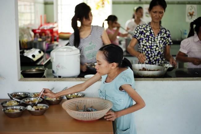 In this photo taken on Wednesday, Aug. 8, 2012, Ho Thi Lang, foreground, helps prepare lunch for other children at a rehabilitation center in Danang, Vietnam. The children were born with physical and mental disabilities that the center's director says were caused by their parents' exposure to the chemical dioxin in the defoliant Agent Orange. On Thursday, the U.S. for the first time will begin cleaning up leftover dioxin that was stored at the former military base that's now part of Danang's airport.
