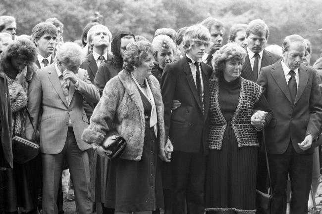 Wiping away a tear (l) is comedian Freddie Starr and his wife Sandy at the requiem mass of actor Alan Lake at the Sacred Heart Catholic Church in Sunningdale. Picture behind Freddie Starr is Max Clifford. Archive-PA211617-6 Ref #: PA.15027776  Date: 17/10/1984