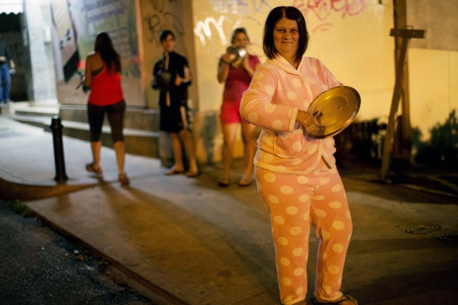 A woman wearing her pajamas bangs on a pot during an anti-government demonstration in the Altamira neighborhood of Caracas, Venezuela, Friday, Feb. 21, 2014. The anti-government movement has appeared to have snowballed into a political crisis, the likes of which Venezuela's socialist leadership hasn't seen since a 2002 coup attempt. Protest rallies are expected throughout the country on Saturday.