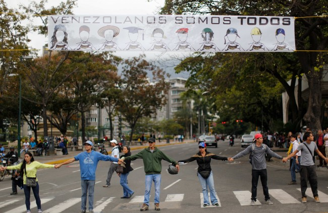 "Demonstrators join hands to block the highway at Altamira neighborhood in Caracas, Venezuela, Monday, Feb. 24, 2014. The banner over their heads reads in Spanish ""We are all Venezuela"". Traffic has come to a halt in parts of the Venezuelan capital because of barricades set up by opposition protesters across major thoroughfares. The protests are part of a wave of anti-government demonstrations that have swept Venezuela since Feb. 12 and have resulted in at least 10 deaths. The protests in the capital Monday were peaceful. Police and National Guard troops stood by but did not act to remove the barricades despite the effect on the morning commute."