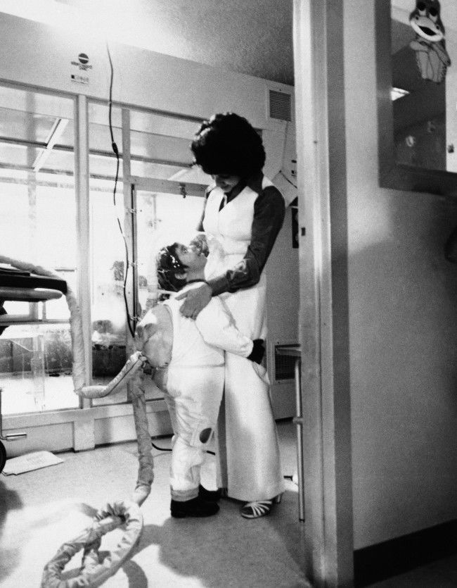 """Little David Vetter, the six-year-old """"bubble baby"""", gives his mother Carol Ann Vetter, a hug while wearing his new Mobile Isolator System, in Houston, Nov. 4, 1977. David suffers from Severe Combined Immune Deficency Syndrome (SCIDS) The suit is a germ-free space type suit that enables David to leave his germ-free bubble that he has lived in since birth. The long hose attached to David's back is a live-support system that pumps air into the suit. ("""