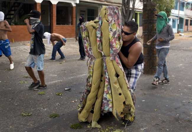 A demonstrator protects himself with an old mattress during clashes with police during an anti-government protest in Valencia, Venezuela, Wednesday, Feb. 26, 2014. The protests began with students and were soon joined by others in several cities, upset over crime, economic problems and heavy-handed government response to the protests.