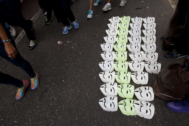 Demonstrators walk past Guy Fawkes masks for sale during an anti-government protest in Caracas, Venezuela, Sunday, March 2, 2014. Since mid-February, anti-government activists have been protesting high inflation, shortages of food stuffs and medicine, and violent crime in a nation with the world's largest proven oil reserves.