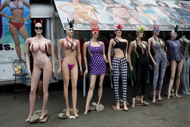 Mannequins wearing carnival masks and swimsuits line the front of a shop near the beach during carnival in La Guaira, Venezuela, Monday, March 3, 2014. Some Venezuelans are taking time off for carnival despite two weeks of nation-wide opposition protests.