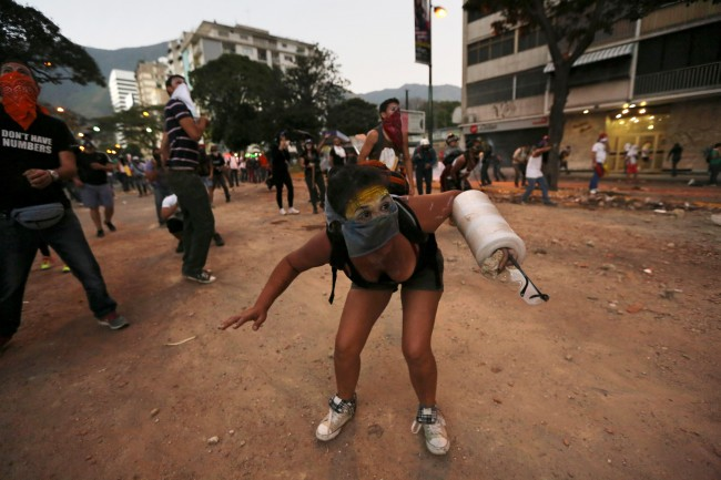 A demonstrator using foam to protect her arm ducks from team gas fired by Bolivarian National Police during clashes in Caracas, Venezuela, Monday, March 3, 2014. Venezuelan opposition leader Henrique Capriles called for citizens to begin organizing committees that could sustain the pressure that continuing street protests have placed on the government of President Nicolas Maduro.