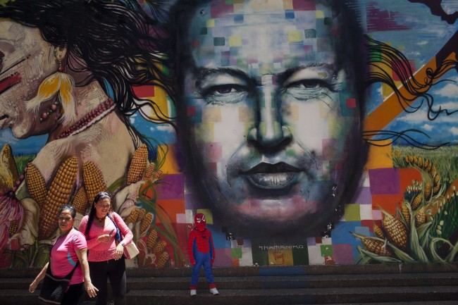 A boy dressed in a Spiderman costume poses for a photo next to a mural of Venezuela's late President Hugo Chavez painted on a wall of the Museo de Bellas Artes in Caracas, Venezuela, Tuesday, March 4, 2014. He's been dead a year, but Chavez's face and voice are everywhere. He bangs out the national anthem on state radio every morning and the national guard has even blasted his voice reciting poetry to drive rock-throwing protesters off the street.