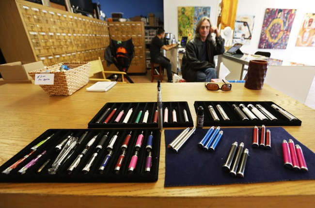 "John Hartigan, right, proprietor of Vapeology LA, sits behind an array of electronic cigarettes at his store in Los Angeles. The Los Angeles City Council voted 14-0 to approve an ordinance to ban e-cigarette use, or ""vaping"" at public places where tobacco smoking is restricted."