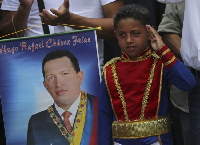 A boy wearing an historical uniform associated with Venezuelan hero Simon Bolivar salutes while standing next to a poster of the late President Hugo Chavez during a military parade commemorating the one year anniversary of Chavez's death, in Caracas, Venezuela, Wednesday, March 5, 2014. The anniversary of Chavez's death was marked with a mix of street protests and solemn commemorations that reflected deep divisions over the Venezuela he left behin