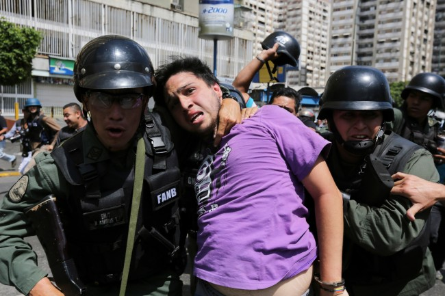 Bolivarian National Guards arrest an anti-government protester in handcuffs during clashes between motorcyclists and protesters in the Los Ruices neighborhood of Caracas, Venezuela, Thursday, March 6, 2014. Venezuelan officials say a National Guard member and a civilian were killed in the clash between residents and armed men who tried to remove a barricade placed by anti-government protesters.