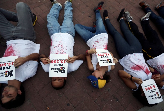 Demonstrators lie on the ground holding statistics about the people murdered in the 14 years of Chavista government, at a protest in Caracas, Venezuela, Friday, March 7, 2014. Venezuela is coming under increasing international scrutiny amid violence that most recently killed a National Guardsman and a civilian. United Nations human rights experts demanded answers Thursday from Venezuela's government about the use of violence and imprisonment in a crackdown on widespread demonstrations.