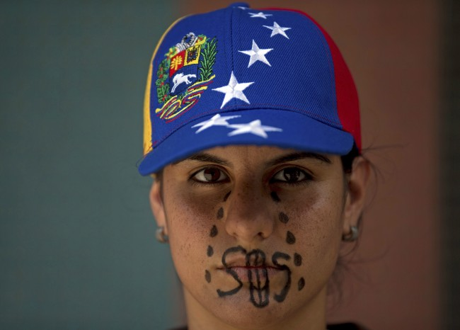 "A woman wearing a cap representing Venezuela's national flag, the SOS distress signal marked across her lips and painted black tears streaming down her face, looks into the camera during a demonstration in Caracas, Venezuela, Saturday, March 8, 2014. Venezuelans returned to the streets for the ""empty pots march"" to highlight growing frustration with shortages of some everyday items. In Caracas, the march was scheduled to end at the country's Food Ministry, but the evening before Caracas' mayor announced that he had not authorized the march."